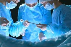 Le groupe de chirurgiens au travail dans le théâtre d'opération a modifié la tonalité dans le bleu Photographie stock libre de droits