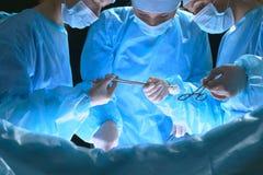 Le groupe de chirurgiens au travail dans le théâtre d'opération a modifié la tonalité dans le bleu Images stock