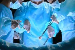 Le groupe de chirurgiens au travail dans le théâtre d'opération a modifié la tonalité dans le bleu Images libres de droits