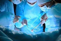 Le groupe de chirurgiens au travail dans le théâtre d'opération a modifié la tonalité dans le bleu Image stock