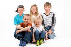 Le groupe de cinq enfants situant sur le plancher Images stock