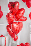 Le groupe de coeur rouge monte en ballon dans un intérieur blanc Photos stock