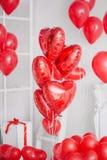 Le groupe de coeur rouge monte en ballon dans un intérieur blanc Images stock