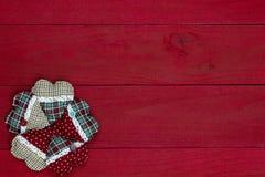 Le groupe de coeurs de Noël de pays de plaid encadrent le fond en bois rouge foncé Photos stock