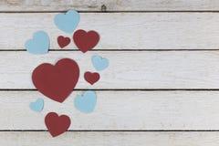 Le groupe de coeurs de papier bleus et rouges s'est étendu sur le fond en bois blanc Photo libre de droits