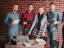 Le groupe de concepteurs avec un presse-papiers discutent l'information image stock