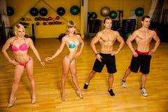 Le groupe de concurrents forment la pose avant competitio de bodybuilding Photos stock