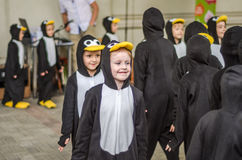 Le groupe de danse de danseurs d'enfants en bas âge exécutent à une partie d'enfants devant l'assistance habillée comme pingouins Photographie stock libre de droits