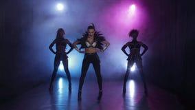 Le groupe de danse de trois filles commencent leur présentation Fond fumeux banque de vidéos