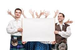 Le groupe de danseurs d'écossais dansent avec la bannière vide Photo stock