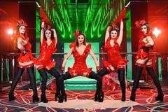 Le groupe de danseurs féminins sexy dans l'assortiment rouge équipe l'exécution Photos libres de droits