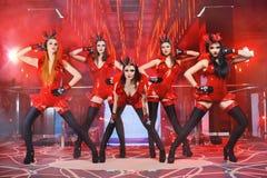 Le groupe de danseurs féminins sexy dans l'assortiment rouge équipe l'exécution Photographie stock