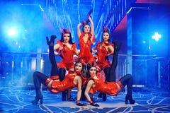Le groupe de danseurs féminins sexy dans l'assortiment rouge équipe l'exécution Image libre de droits