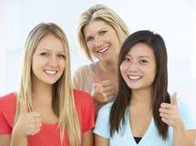 Le groupe de femmes d'affaires heureuses et positives dans le tenue décontractée faisant des pouces lèvent le geste Photographie stock libre de droits