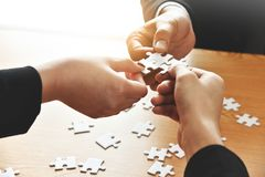Le groupe de gens d'affaires de mains relient le puzzle denteux Photo libre de droits