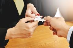 Le groupe de gens d'affaires de mains relient le puzzle denteux Photographie stock