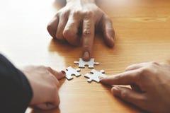 Le groupe de gens d'affaires de mains tiennent le puzzle denteux Photos stock
