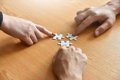 Le groupe de gens d'affaires de mains tiennent le puzzle denteux Image stock