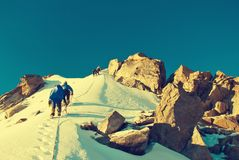 Le groupe de grimpeurs atteint le dessus de la crête de montagne S'élever et photographie stock libre de droits