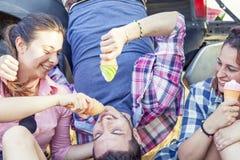 Le groupe de jeunes adultes rendent fou et mangent la crème glacée  Photographie stock