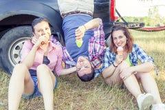 Le groupe de jeunes adultes rendent fou et mangent la crème glacée  Images stock