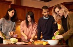 Le groupe de jeunes amis ethniques multi dans la cuisine se préparent à la partie Images libres de droits