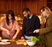 Le groupe de jeunes amis ethniques multi dans la cuisine se préparent à la partie Photographie stock libre de droits