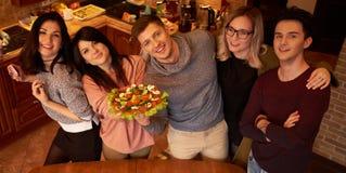 Le groupe de jeunes amis ethniques multi dans la cuisine se préparent à la partie Image libre de droits