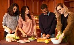 Le groupe de jeunes amis ethniques multi dans la cuisine se préparent à la partie Photographie stock