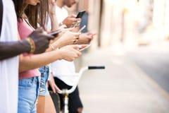 Le groupe de jeunes amis de hippie à l'aide du téléphone intelligent à urbain sont Photo libre de droits