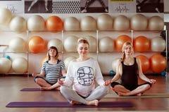 Le groupe de jeunes femmes enceintes faisant la relaxation s'exercent sur l'exerc image stock