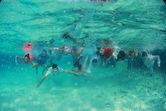 Le groupe de jeunes heureux d'amis nagent plongeant sous l'eau avec les jeunes mariés nuptiales de couples près de eux le mariage Photographie stock
