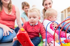 Le groupe de jeunes mères heureuses observant leurs bébés mignons et en bonne santé jouent Photo libre de droits