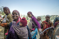 Le groupe de jeunes mamans travaillantes portent le nourrisson sur leur sourire arrière tout en faisant la routine de travail au  Images libres de droits