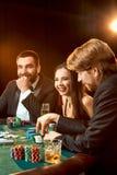 Le groupe de jeunes riches joue le tisonnier dans le casino Images libres de droits
