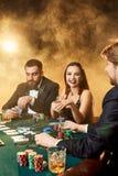 Le groupe de jeunes riches joue le tisonnier dans le casino Photographie stock