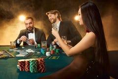 Le groupe de jeunes riches joue le tisonnier dans le casino Photos stock