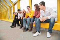 Le groupe de jeunes s'asseyent sur la passerelle Images libres de droits