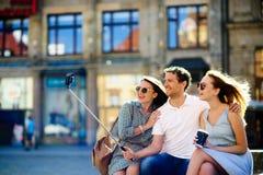 Le groupe de jeunes touristes fait le selfie sur le fond d'un vieux bâtiment Photographie stock
