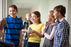 Le groupe de l'école badine avec des boîtes de soude dans le couloir Photographie stock libre de droits