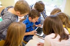 Le groupe de l'école badine avec le PC de comprimé dans la salle de classe Image libre de droits