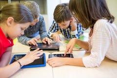 Le groupe de l'école badine avec le PC de comprimé dans la salle de classe Images libres de droits