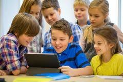 Le groupe de l'école badine avec le PC de comprimé dans la salle de classe Photos libres de droits