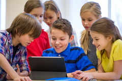 Le groupe de l'école badine avec le PC de comprimé dans la salle de classe Photo libre de droits