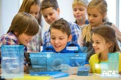 Le groupe de l'école badine avec le PC de comprimé dans la salle de classe Photo stock