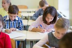 Le groupe de l'école badine l'essai d'écriture dans la salle de classe Image libre de droits