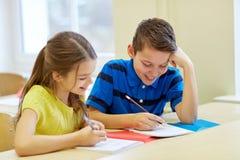 Le groupe de l'école badine l'essai d'écriture dans la salle de classe Images libres de droits