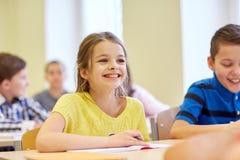 Le groupe de l'école badine l'essai d'écriture dans la salle de classe Images stock