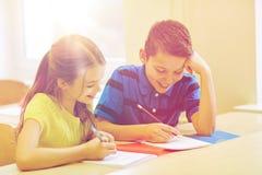 Le groupe de l'école badine l'essai d'écriture dans la salle de classe Image stock