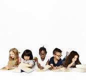 Le groupe de l'école badine la lecture pour l'éducation photo stock